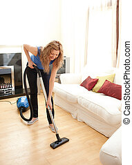 Charming woman use vacuum cleaner