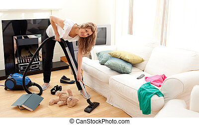 Enthusiastic woman in her chaotic living room with a vacuum...