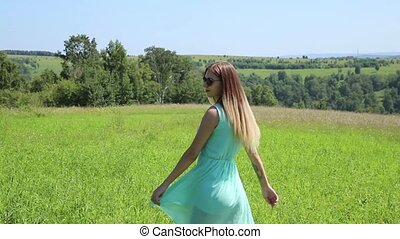 young beautiful girl circling on the green field.