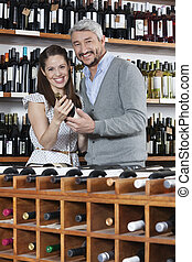 Portrait Of Couple With Wine Bottles Standing At Rack -...