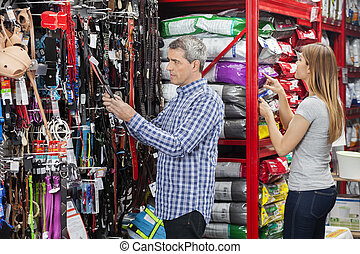 Couple Shopping At Pet Store - Couple buying pet food and...