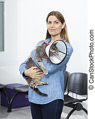 Mid Adult Woman Holding Cat With Cone In Clinic - Portrait...