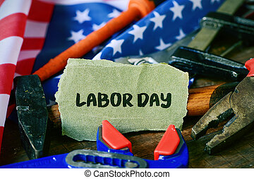 tools, American flag and text labor day - closeup of a piece...