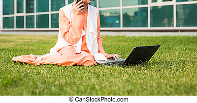 beautiful young Muslim girl sitting with notebook outdoor