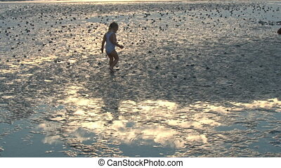 Little Girl Plays in Sea Water against Beach at Sunset
