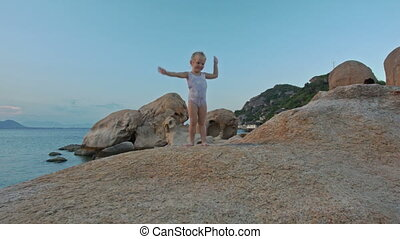 Little Girl Stands on Rock Top Waves Hands at Sunset on Beach