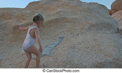 Little Girl Climbs up Large Bare Rock at Sunset on Beach -...
