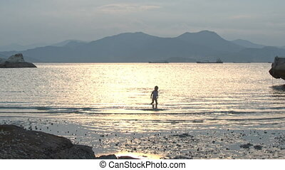 Little Girl Swims in Sea Sun-path against Hill at Sunset