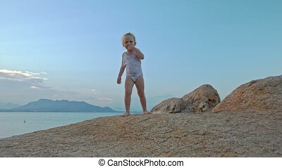 Little Girl Climbs Down Large Bare Rock at Sunset on Beach