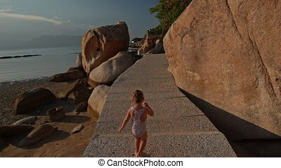Little Girl Runs along Rocky Path on Beach against Azure Sea...