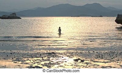 Little Girl Runs along Wet Sand Beach at Low Tide at Sunset...