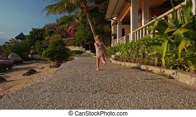 Backside Little Girl Runs along Rocky Path on Beach -...