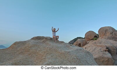 Little Girl Sits on Large Bare Rock Top at Sunset on Beach