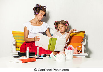 Little girl sitting with her mother and looking at a photo album