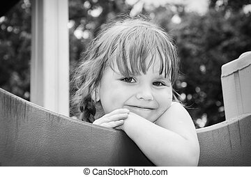 In the summer at the playground smiling little girl. Black and white photo.