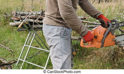 Man sawing a branch with the help of an chain saw, firewood...