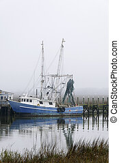 Shrimp Boat in the Marsh - A shrimp boat docked at a pier.