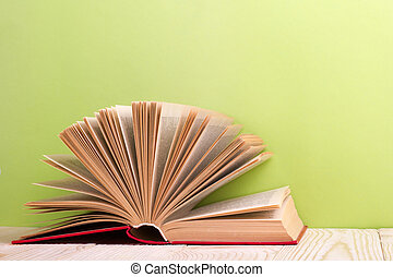 Open book on green wooden background. Education concept. Copy space for ad