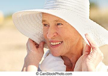 happy senior woman in sun hat on summer beach - age, leisure...