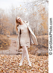 woman in the park - happy blond woman walking in the autumn...