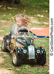 The little baby girl playing at car against green grass