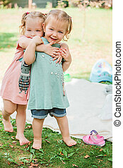 The two little baby girls playing against green grass - The...