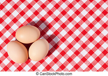 three eggs on picnic tablecloth