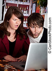 Woman and man staring with shock at laptop computer