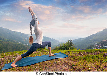 Woman doing yoga asana Virabhadrasana 1 - Warrior pose outdoors