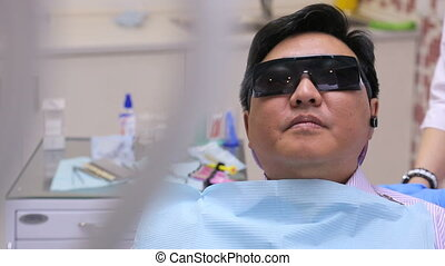 Dentist takes pictures with camera, patient sitting in a...