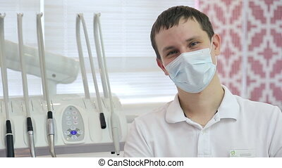 Young professional in field of dentistry in mask sitting next to dental unit.
