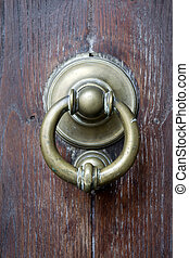 brass knocker on a wooden main door - old brass knocker on a...