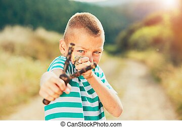 Boy with slingshot - Naughty boy holding slingshot with...