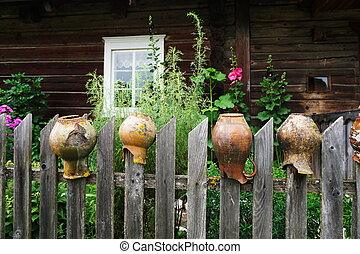 old jugs on  wooden fence near  rural house