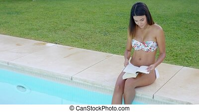 Pretty young woman relaxing with a book sitting on the edge...