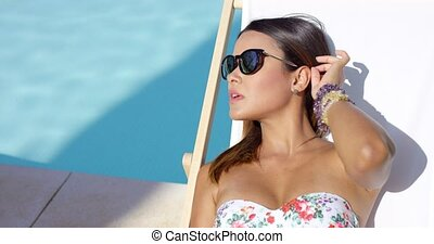 Pretty young brunette woman sunbathing poolside in a deck...