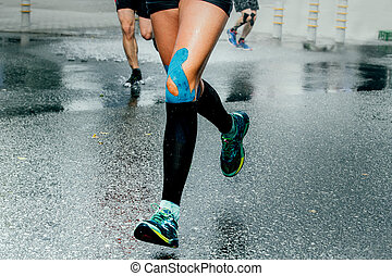 feet girl runners in compression socks and taping on his...