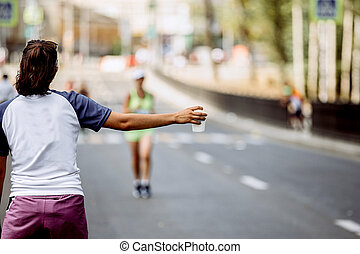 girl in hand a cup of at water point of marathon