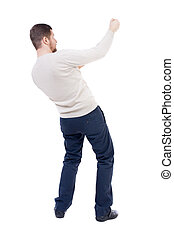 back view of standing man pulling a rope from the top or...