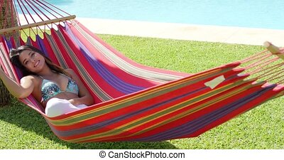 Smiling young woman laying down in hammock with colorful...