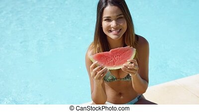 Happy woman at edge of pool eating watermelon - Single...