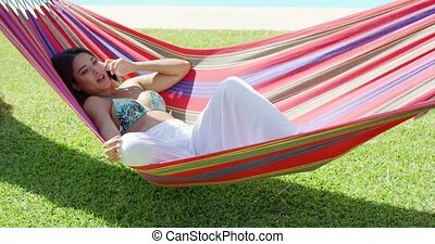 Woman talking on phone while relaxing in hammock - Beautiful...
