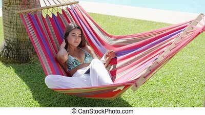 Single woman in bikini reading a book in hammock - Beautiful...