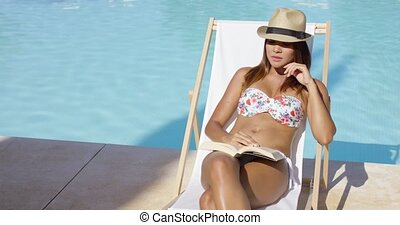Trendy young woman reading a book poolside - Trendy young...