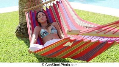 Relaxing young woman in colorful hammock - Single calm young...