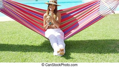 Woman sipping coconut drink in hammock - Cute young woman in...