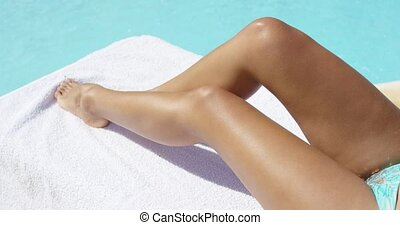 Tanned legs of a young woman sunbathing at the edge of a...
