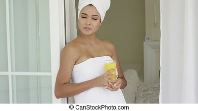 Gorgeous woman wrapped in towel outside with glass of orange...