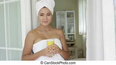 Beautiful woman wrapped in towel looking outside