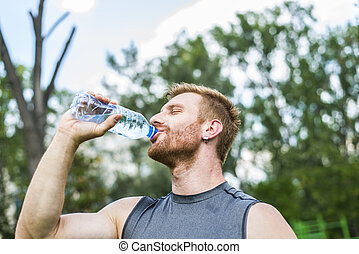 Drinking water - Young athlete drinking water after a...
